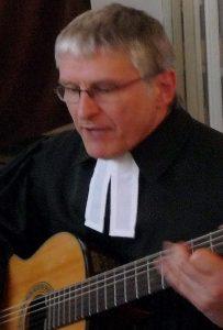Pfarrer Schütz begleitet ein Lied zur Gitarre