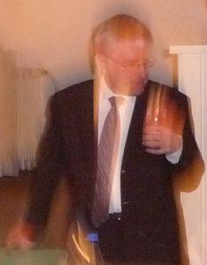 Verwischtes Bild von Pfarrer Schütz mit einem Abendmahlskelch