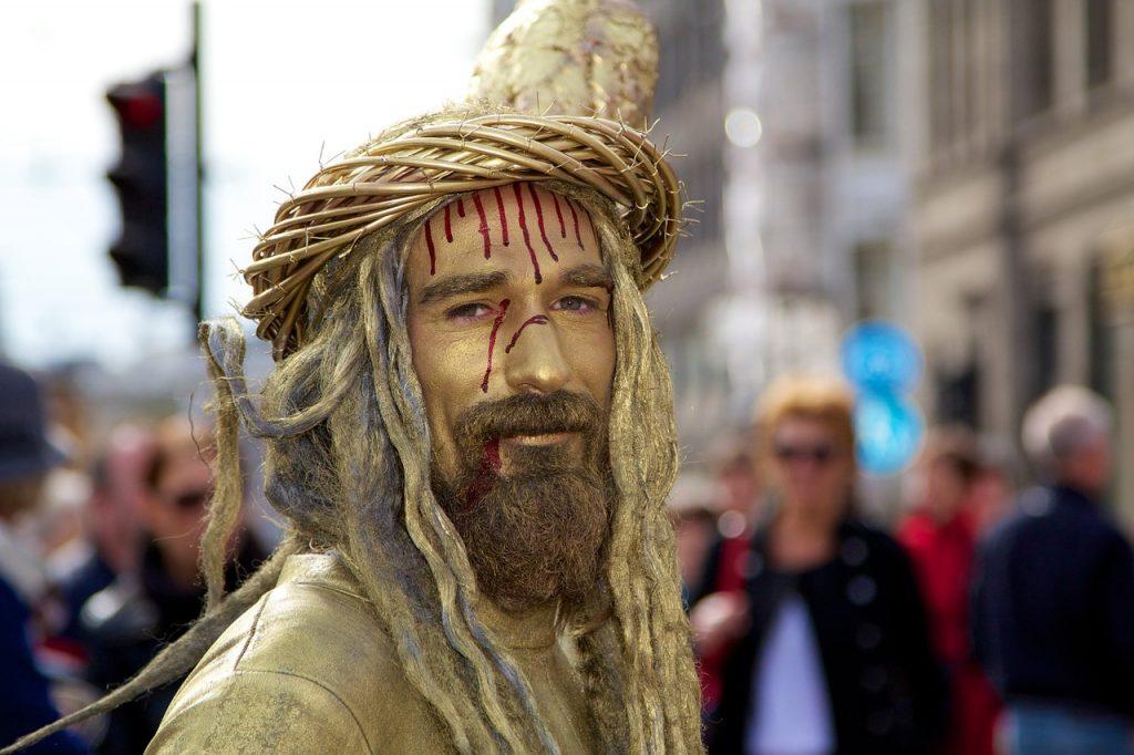 Jesusdarsteller in Goldhaar und Goldkleidung und Dornenkrone, mit Blut im Gesicht