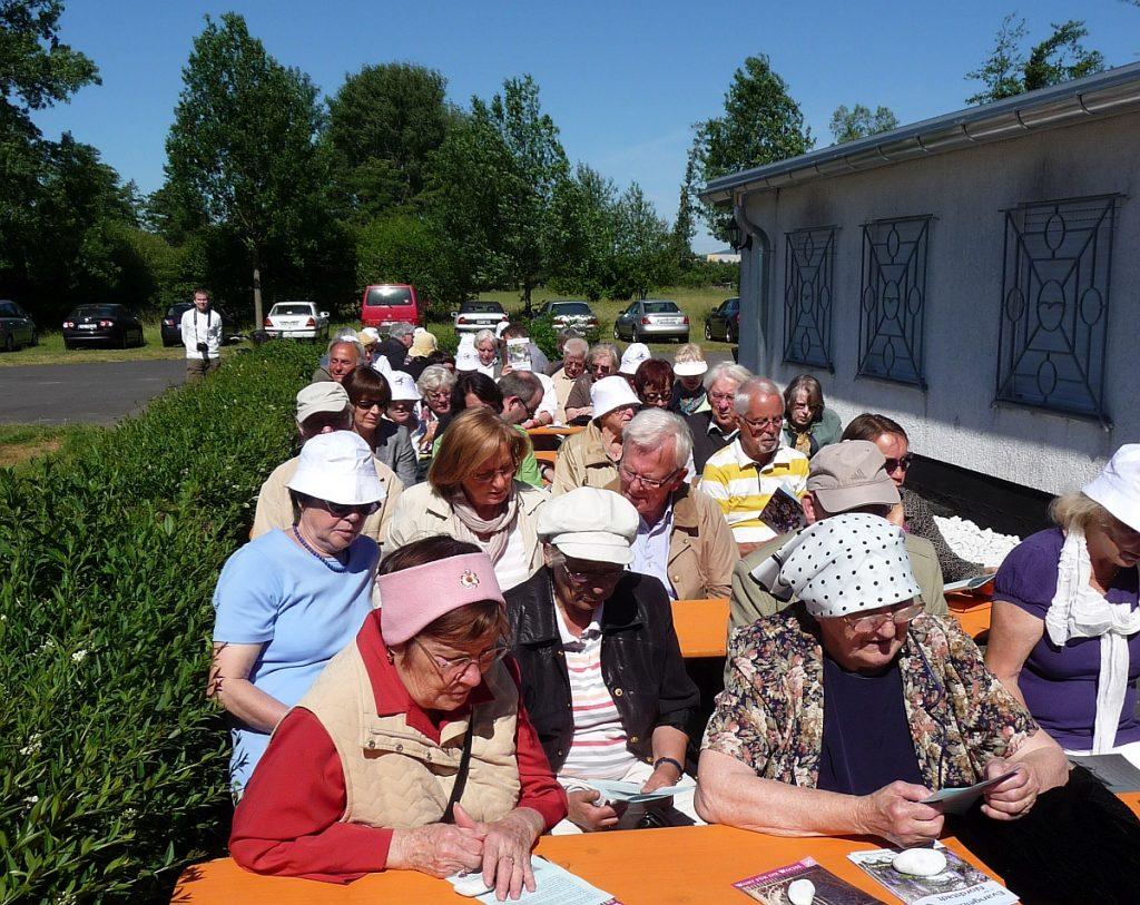 Teilnehmer am Himmelfahrtsgottesdienst neben dem Vereinsheim des Flugsportvereins Gießen