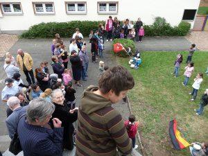 Kinder vielfältiger Herkunft präsentieren auf dem Rasen Lieder