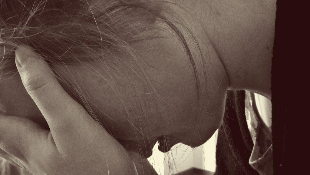 Eine Frau stützt ihr Gesicht auf ihre Hand und weint
