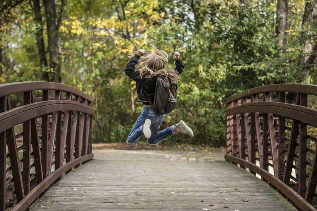 Luftsprung eines Kindes auf einer Brücke