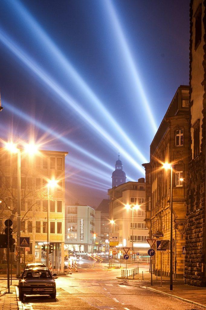 Straße einer Großstadt mit gleißenden Lichtstrahlen am Himmel und sternförmigem Lichtschein der Straßenbeleuchtung