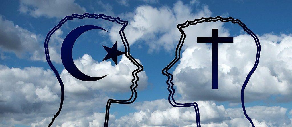 Die Silhouetten zweier männlicher Gesichter, die einander gegenüberstehen, im linken Kopf ist das Symbol des Islam, Halbmond und Stern, zu sehen, im rechten das christliche Kreuz
