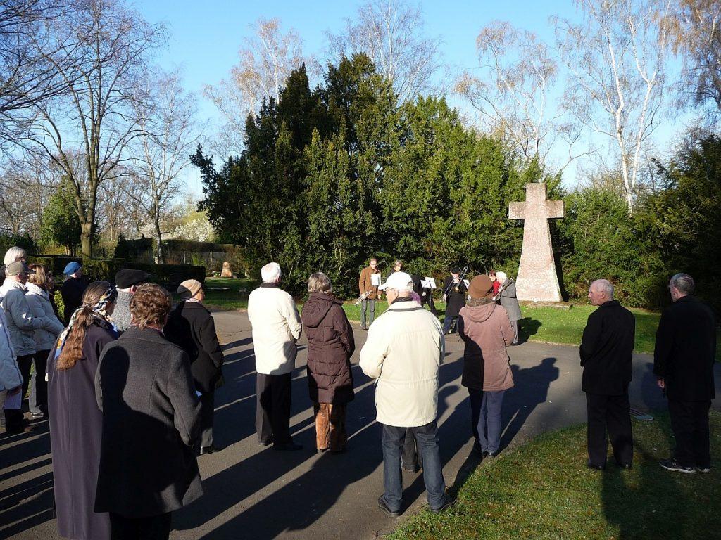 Versammelte Gemeinde unter blauem Himmel am Steinkreuz auf dem Friedhof