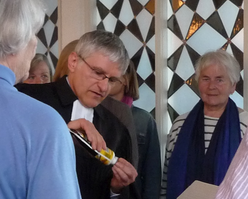 Pfarrer Schütz streicht Klebstoff auf einen Mosaikstein