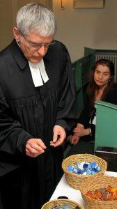 Pfarrer Schütz sucht einen Mosaikstein aus