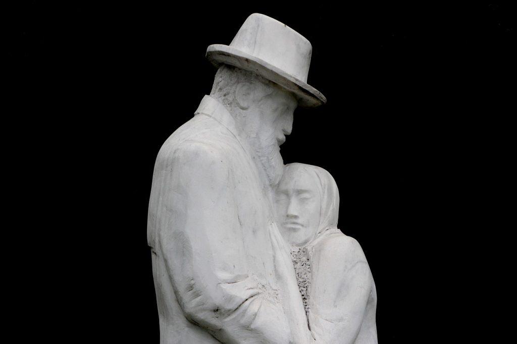 Eine kleine alte Frau schmiegt sich an einen großen alten Mann mit Hut