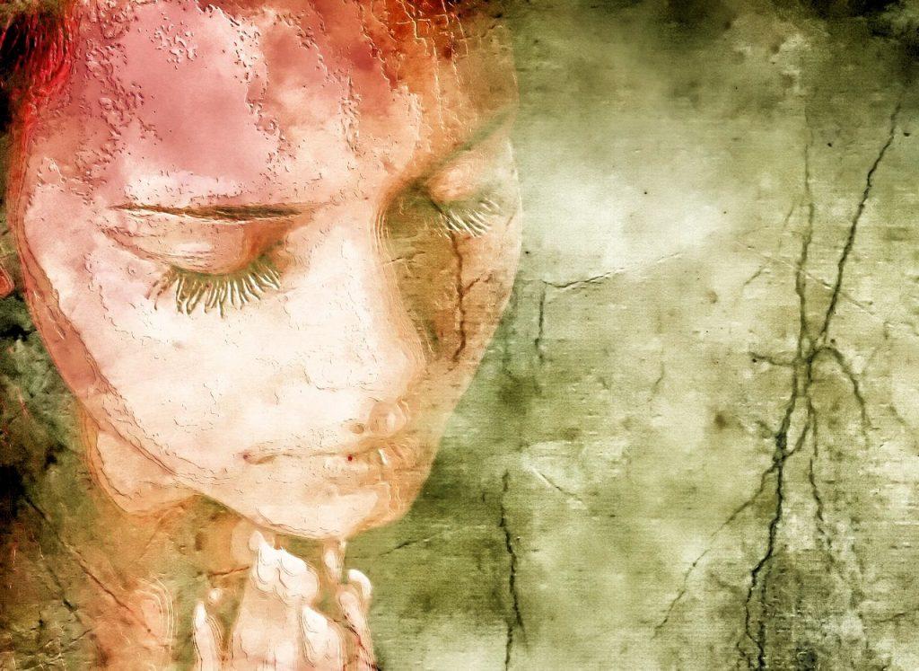 Das Gesicht einer verzweifelt aussehenden Frau mit niedergeschlagenem Blick und gefalteten Händen vor einer rissigen Tapete