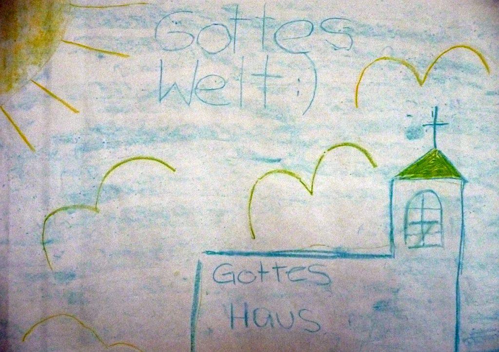 """Auf der Kirche steht: """"Gottes Haus"""", darüber steht am blauen Himmel zwischen Sonne und Wesen mit ausgebreiteten Flügeln: """"Gottes Welt :)"""""""