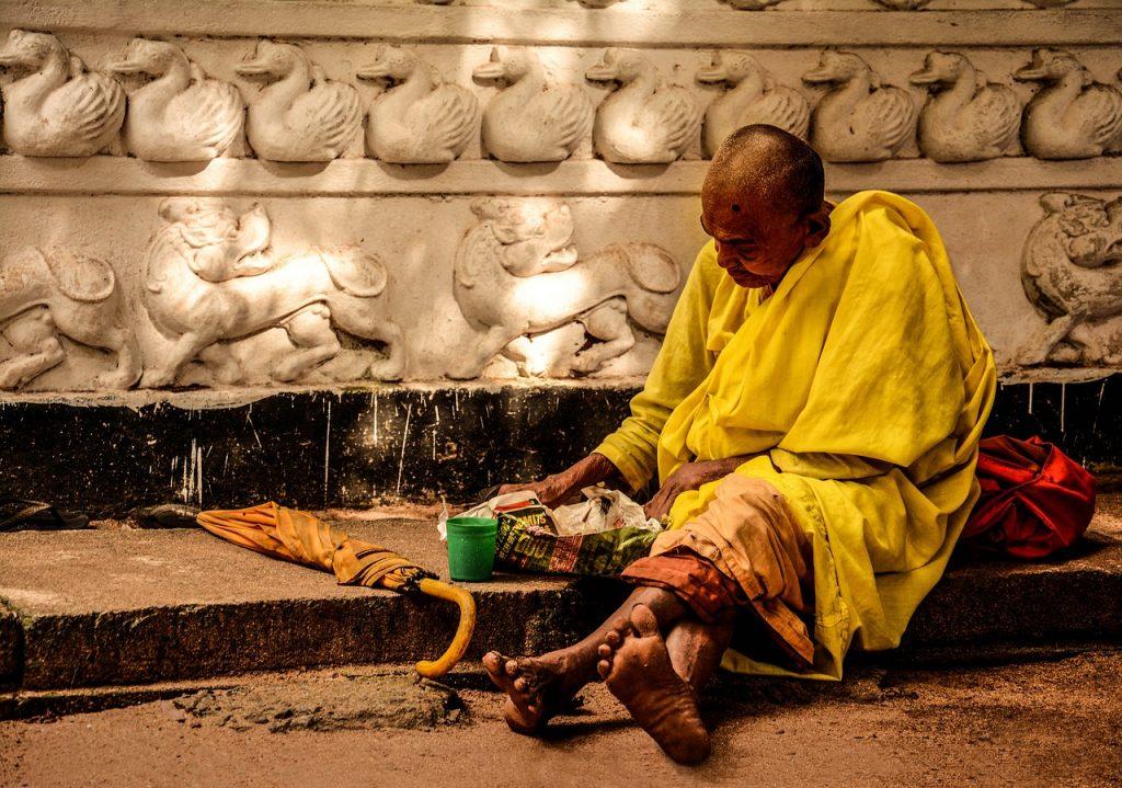 Ein Bettler in gelbem Gewand auf dem Bordstein eines Weges vor einer Mauer, die mit Löwen und Schwänen geschmückt ist