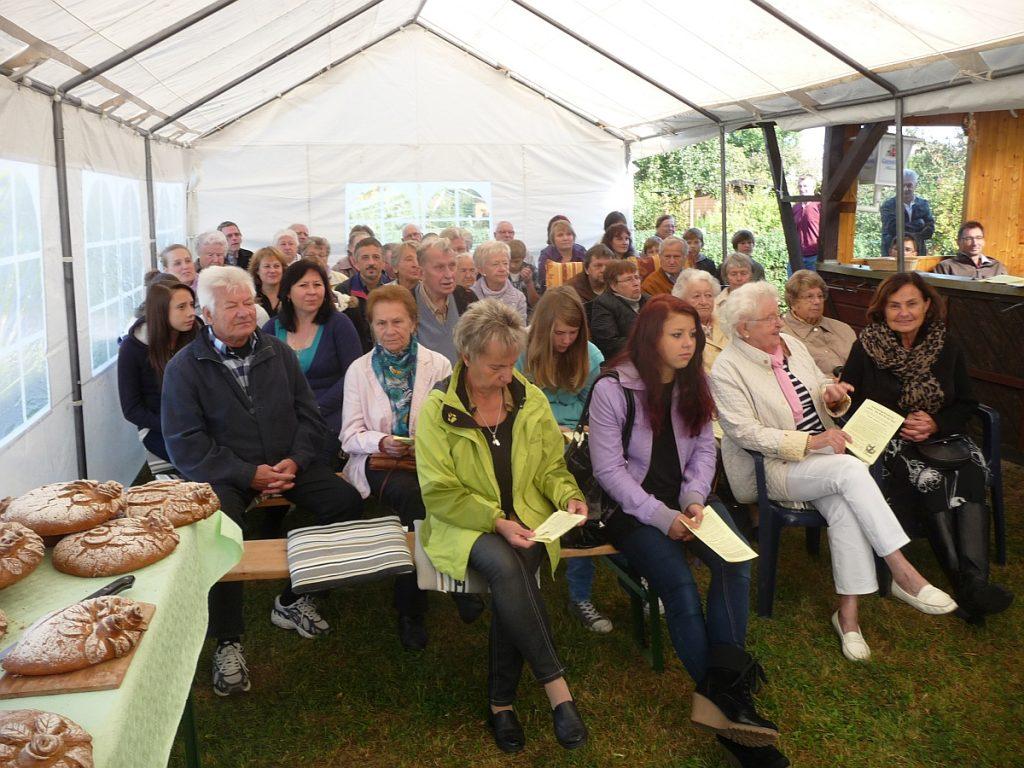 Die Gemeinde sitzt auf den Bierzeltgarnituren im Zelt