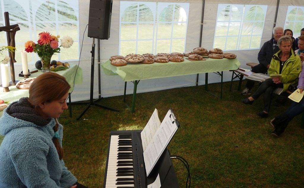 Dina Zavodovska sitzt am Keyboard - auf dem Tisch stehen die von den Konfis gebackenen Brote