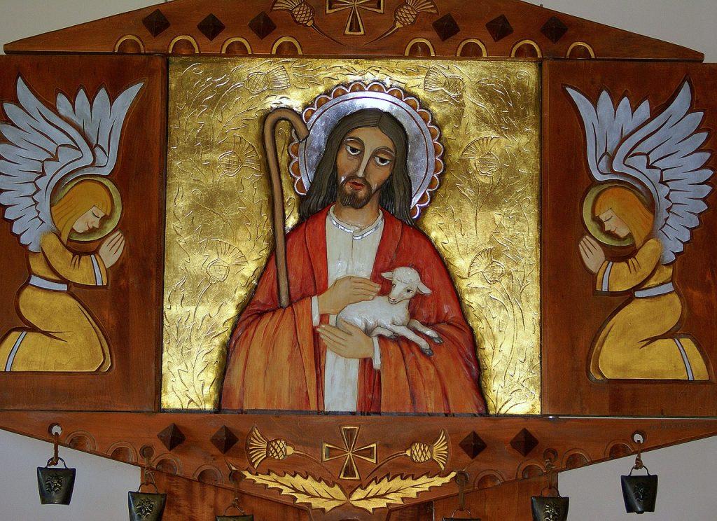 Jesus, der gute Hirte (vor goldenem Hintergrund), streichelt ein Schäfchen, das er auf dem Arm trägt, und zwei Engel beten ihn an