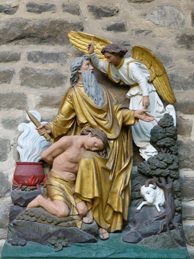 Abraham steht mit dem Messer neben dem gebundenen Sohn Isaak, der seinen Blick senkt, während ein Engel Auge in Auge mit Abraham mit den Finger nach oben weist und mit der anderen Hand auf ein Opferschaf weist