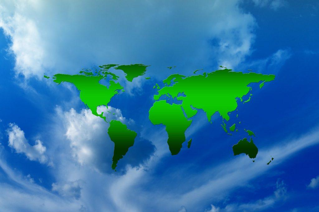 Die Weltkarte vor einem blauen, weiß bewölkten Himmel