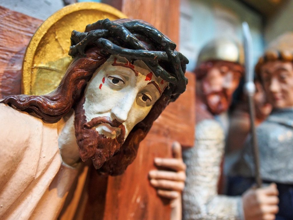 Kreuz tragender Jesus mit Dornenkrone und Blut im Gesicht, im Hintergrund Soldaten
