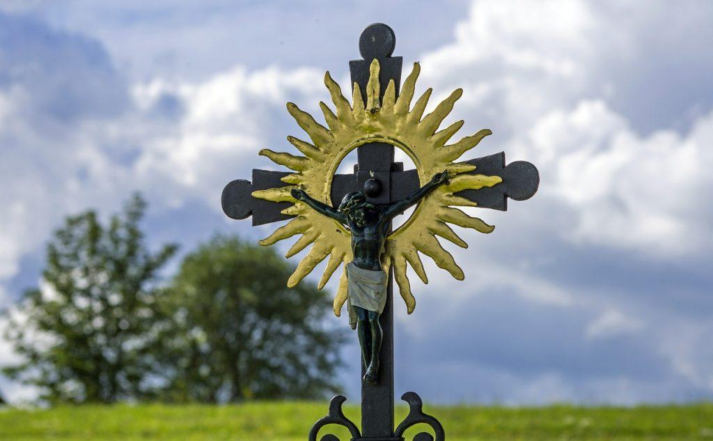 Ein Kruzifix vor wolkigem Himmel mit dem Strahlenkranz einer Sonne um Jesu Kopf