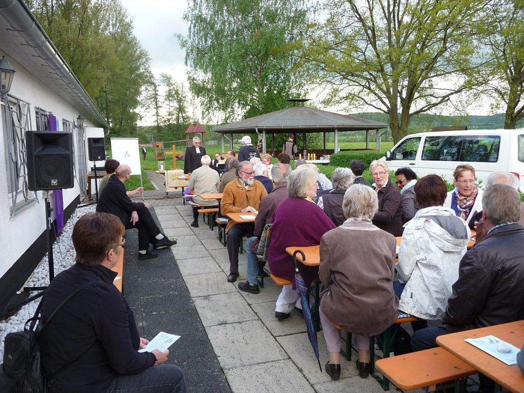 Gottesdienstbesucher auf den Bierzeltgarnituren am Vereinsheim des Flugsportvereins Gießen