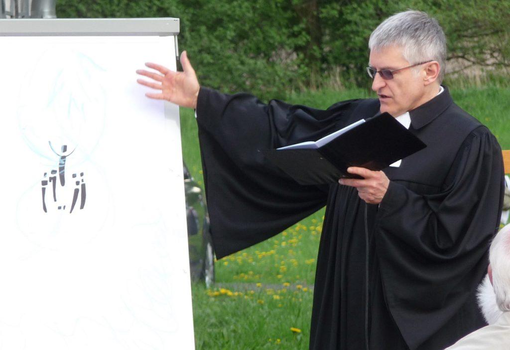 Pfarrer Helmut Schütz zeigt auf die Flip-Chart