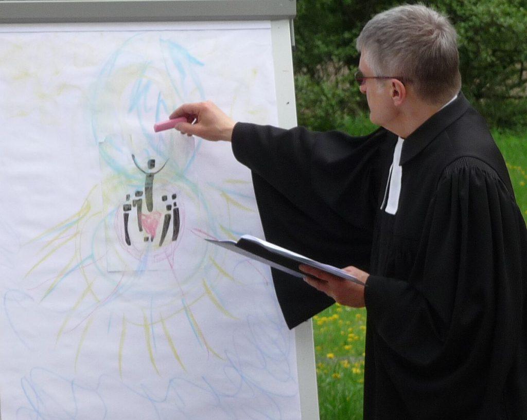 Pfarrer Schütz schreibt mit roter Kreide auf die Flip-Chart