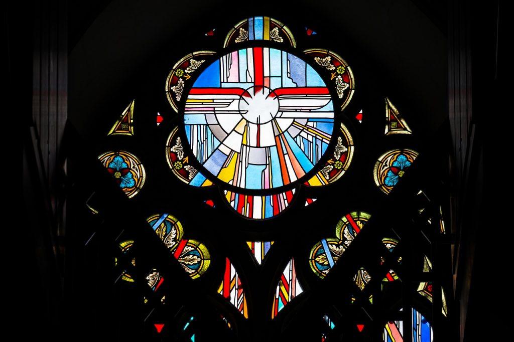 Ein Kirchenfenster, das stilisiert eine Taube und Lichtstrahlen zeigt und wohl den Heiligen Geist symbolisiert