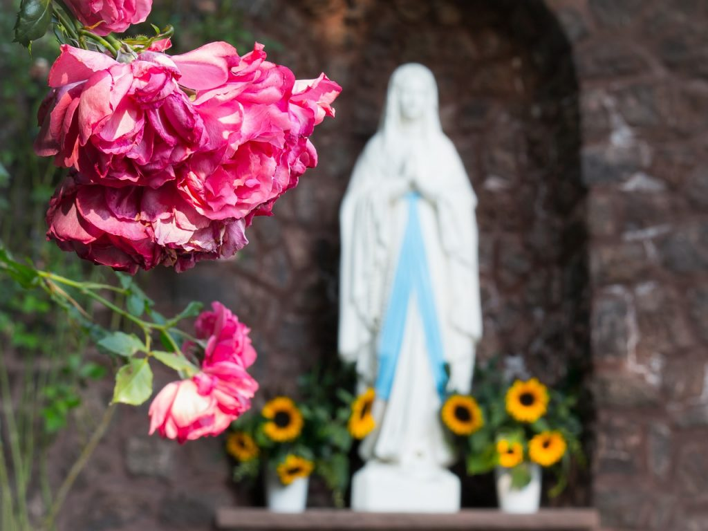 Eine Marienstatue im Hintergrund von Rosen