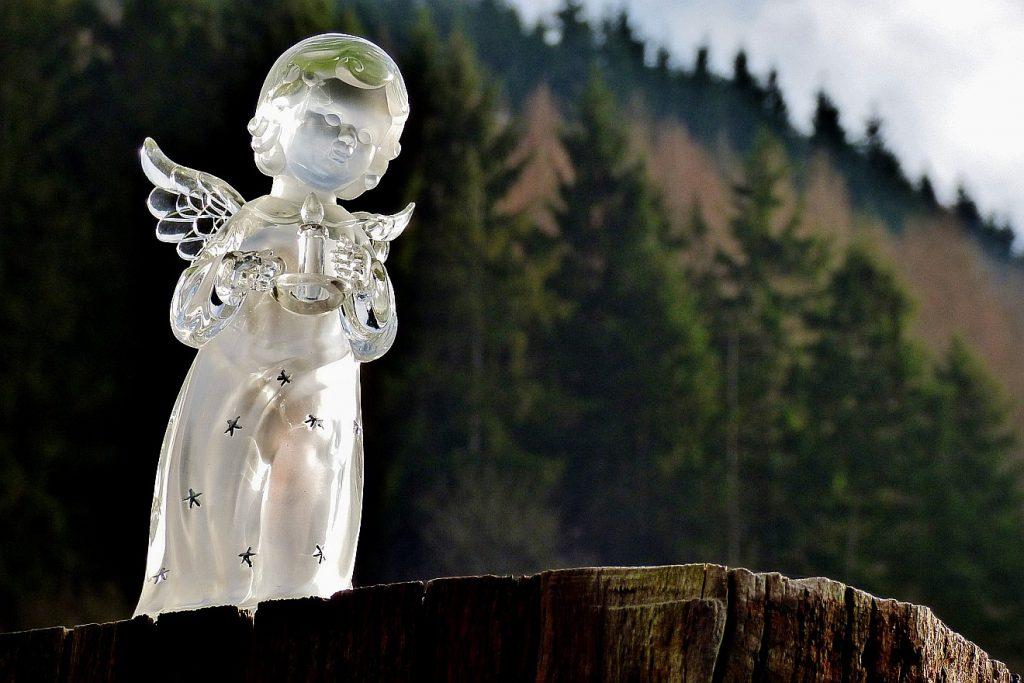 Ein Engel mit Flügeln aus Glas vor einer Waldlandschaft auf einem Baumstumpf