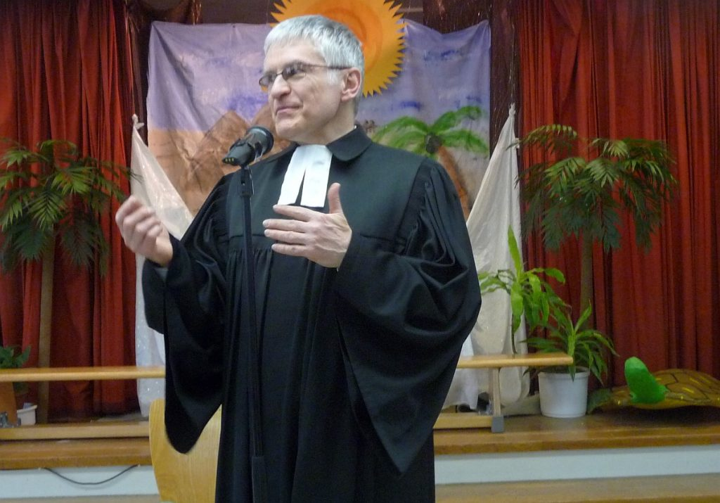 Pfarrer Helmut Schütz erläutert den mehrsprachigen Kehrvers des ersten Liedes