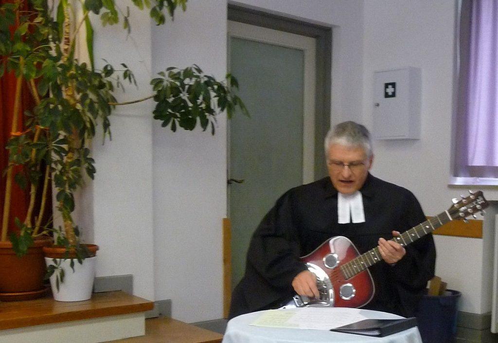 """Pfarrer Schütz begleitet auf der Gitarre das Lied """"Dann gehen Gott und die Menschen Hand in Hand"""""""
