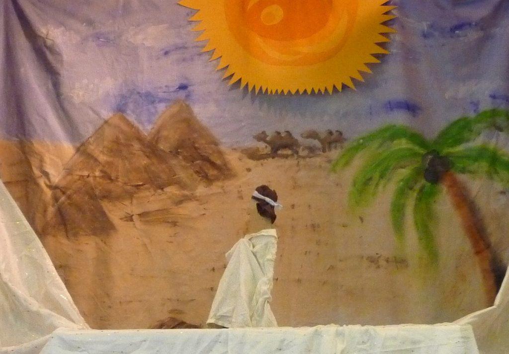 Auf diesem und den folgenden Bildern sind im Hintergrund Berge und eine heiße Wüstensonne zu sehen, im Vordergrund ein Beduine und eine Palme