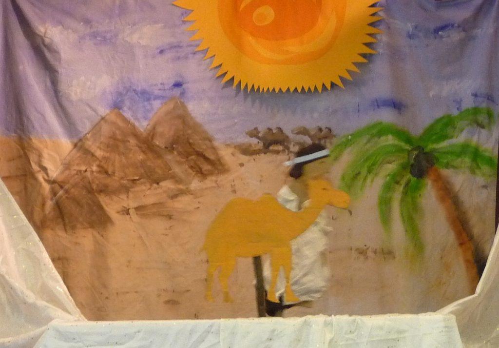 Im Vordergrund ein Beduine mit einem Kamel