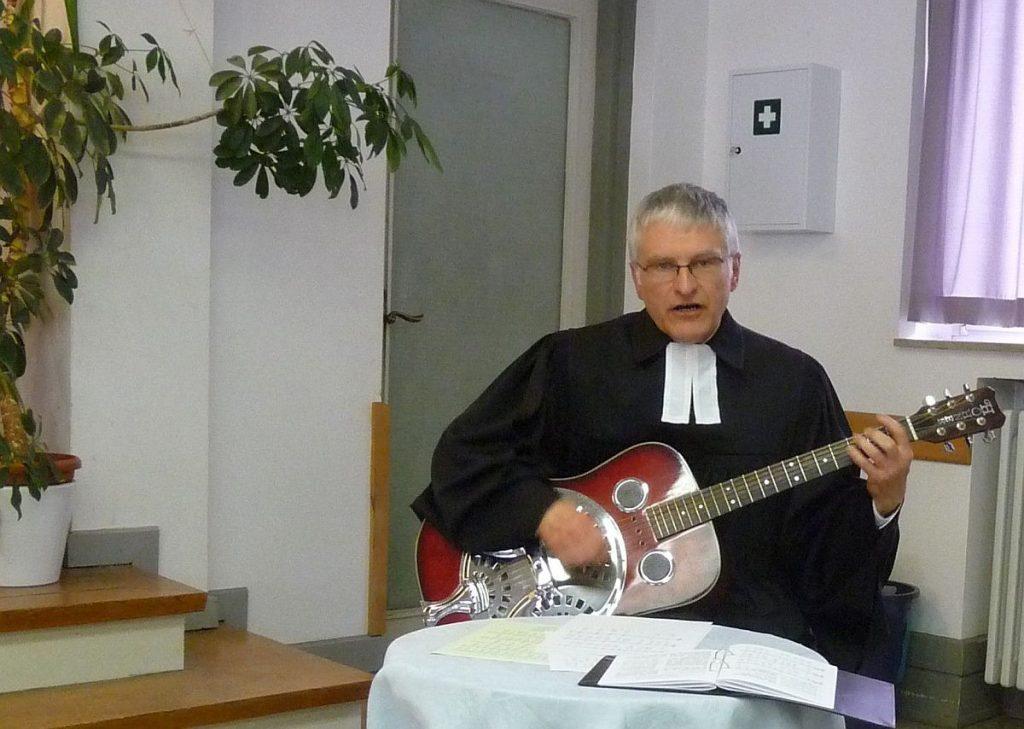 Pfarrer Schütz begleitet mit der Gitarre ein gemeinsames Lied