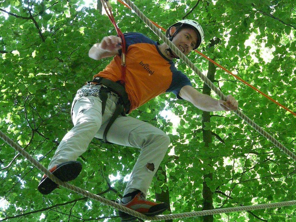 Ein Mann auf und zwischen den Seilen im Kletterwald