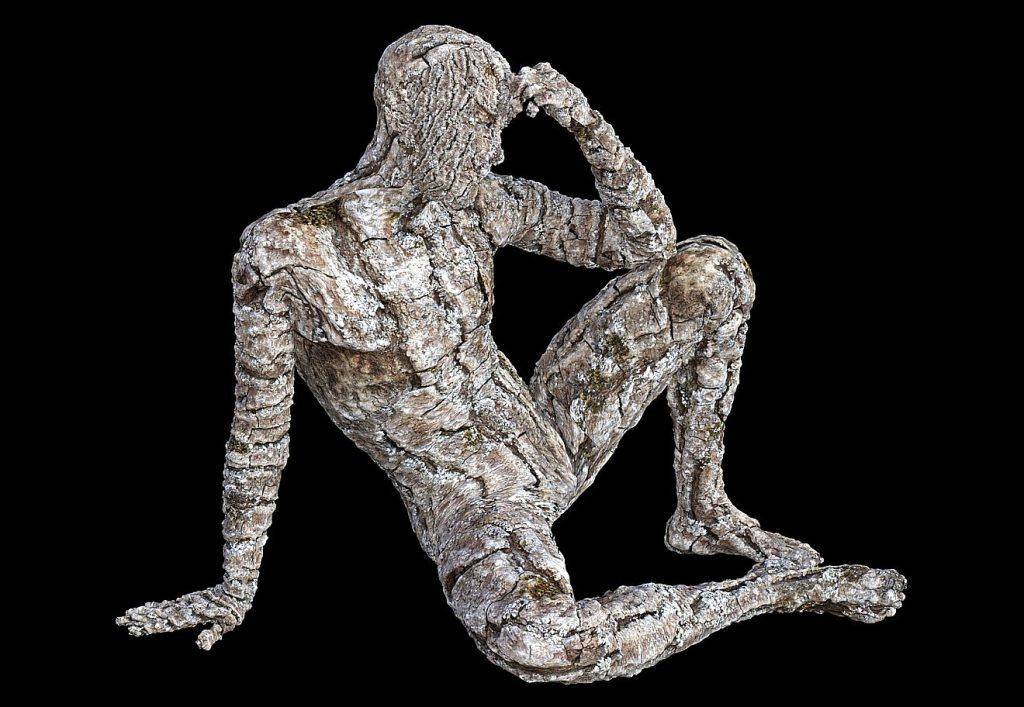 Die Skulptur eines nachdenklichen Mannes aus Birkenrinde, der auf dem Boden hockt, den Ellbogen aufs Knie gestützt, mit der Hand am Kopf