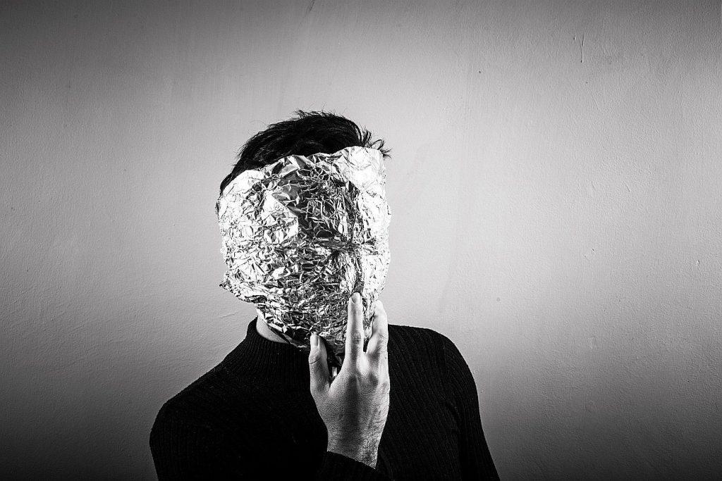 Ein Mann hat Alufolie vor dem Gesicht, um seine Identität zu verbergen - auch eine Art Gesichtskolter