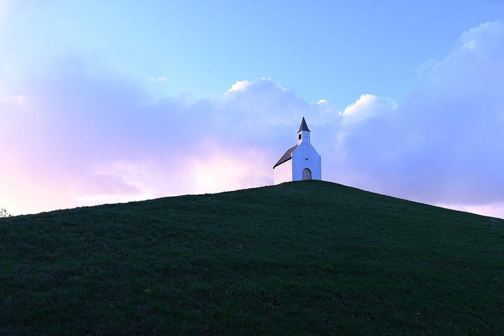 Mach uns ein Zeichen: eine kleine Kirche im Licht auf einem Hügel
