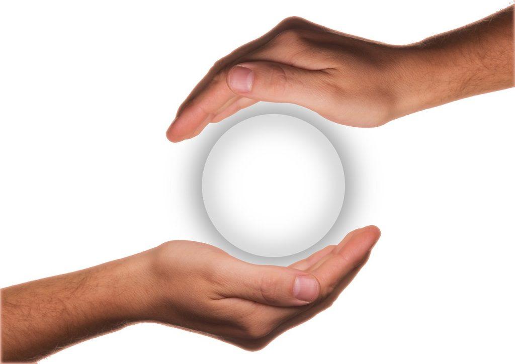 Zwei Hände, eine von oben und eine von unten, schützen eine weiße Kugel