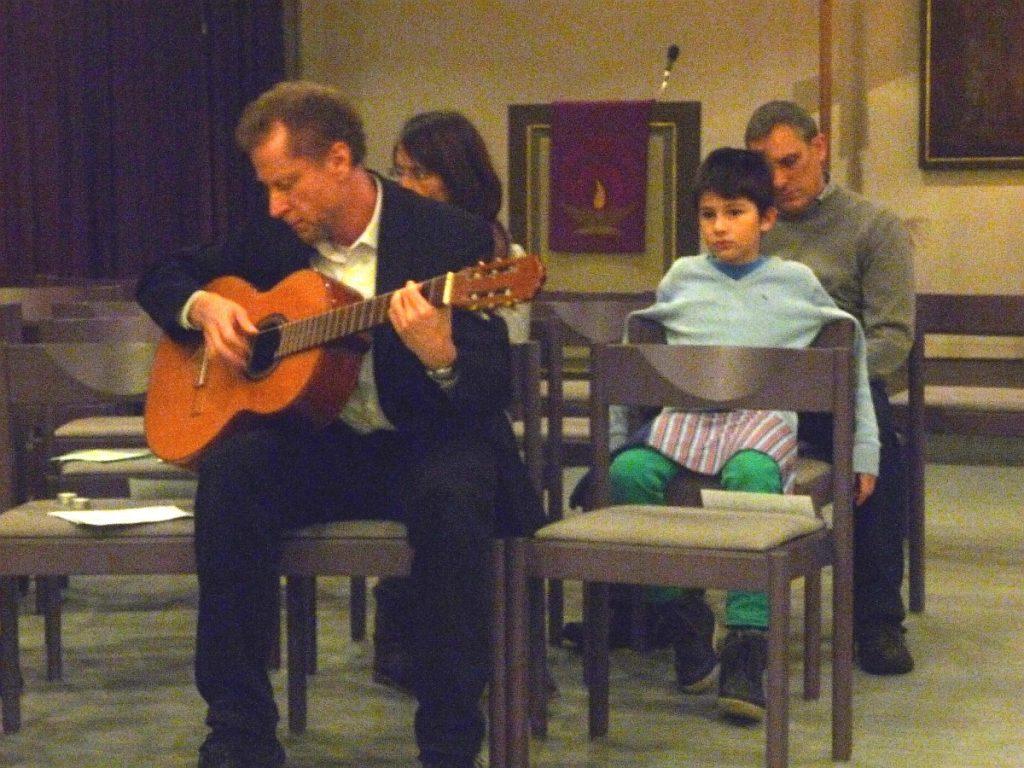 Dr. Ulrich Müller singt ein lateinamerikanisches Lied zur Gitarre