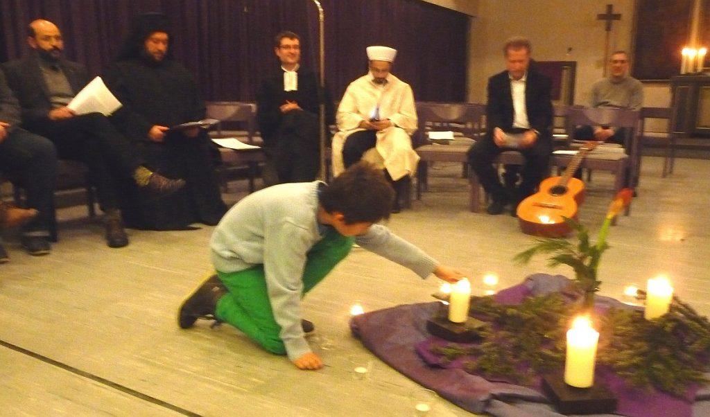 Ein Junge zündete für jedes einzelne Friedensgebet der Religionen in der Mitte eine Kerze an