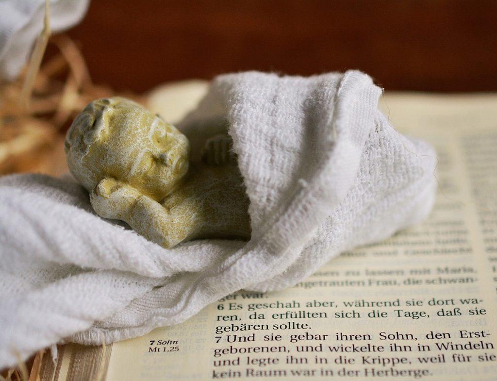 Kleine Christkindskulptur in einer Windel - auf einer aufgeschlagenen Bibel liegend