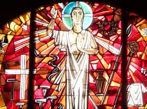 Der auferstandene Jesus auf dem Altarfensterbild der evangelischen Pauluskirche Gießen mit dem Kreuz, den Nägeln, Dornenkrone, Lanze, Stab mit Essigschwamm und weißem Gewand im Hintergrund