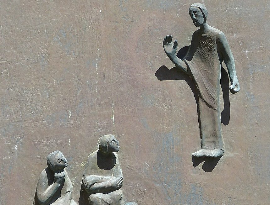 Christus als Lehrer von drei relativ gelangweilt hockenden Figuren als Relief an einer Kirchentür