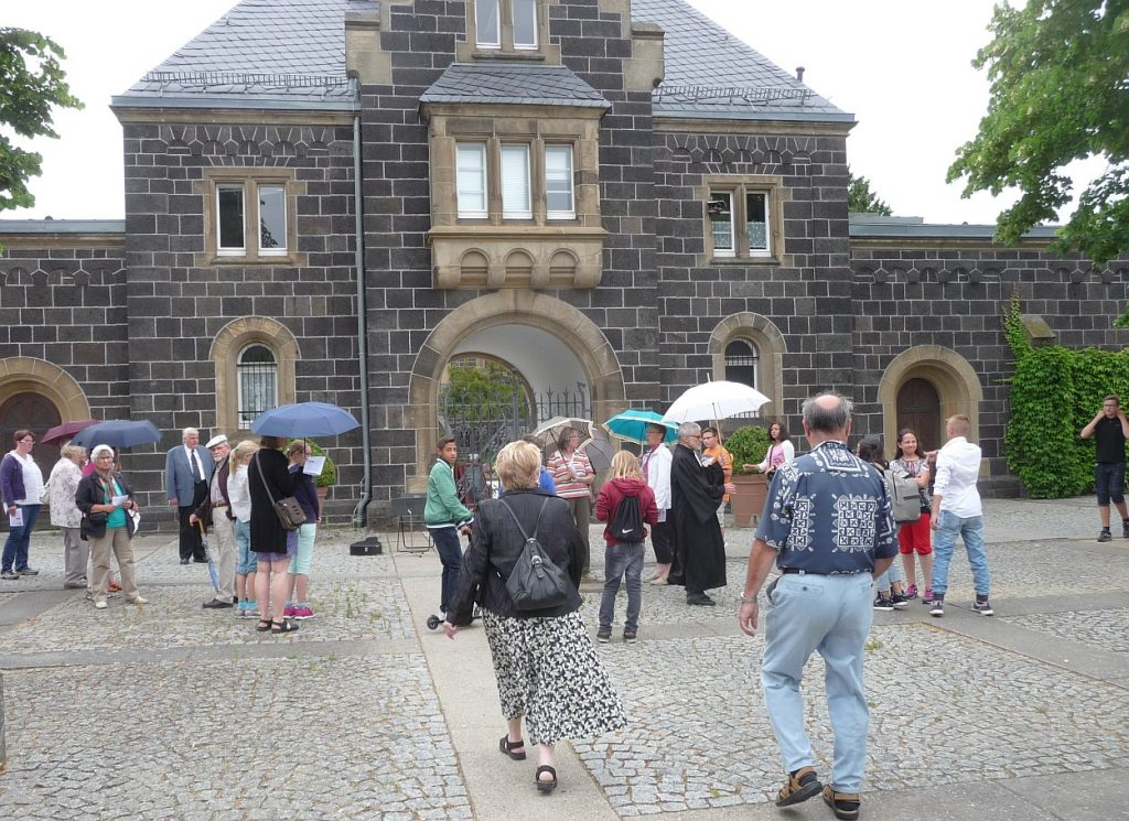 Gottesdienstbesucher kommen am Friedhofsvorplatz an