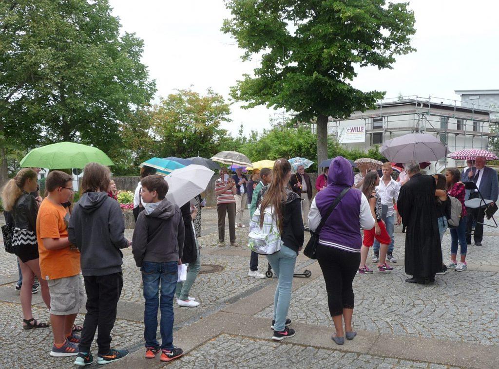 Treffpunkt der Gottesdienstbesucher mit Regenschirmen