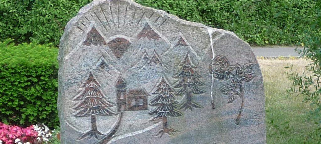 Sonnenuntergang oder -aufgang hinter Bergen, Bäumen und einer Kapelle auf einem Grabstein