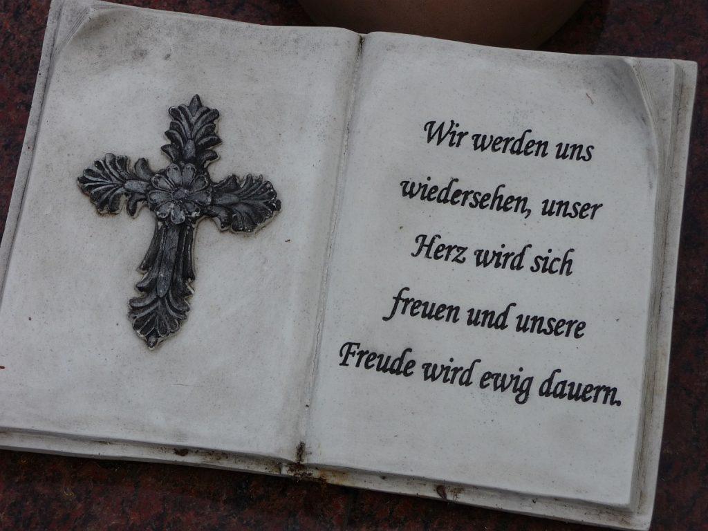 """Auf einem Grabstein ein aufgeschlagenes Buch aus Marmor: links ein Kreuz, rechts """"Wir werden uns wiedersehen..."""""""