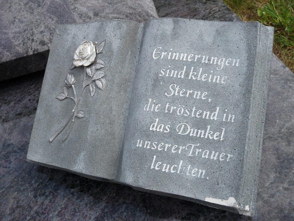 """Aufgeschlagenes Buch als Grabstein: links Rose, rechts """"Erinnerungen sind kleine Sterne..."""""""