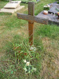 Holzkreuz mit schlichtem Grabschmuck